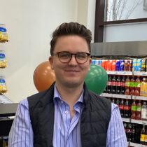 Johannes som driver Täby Parks nya närlivs står framför en del av sina varor i butiken