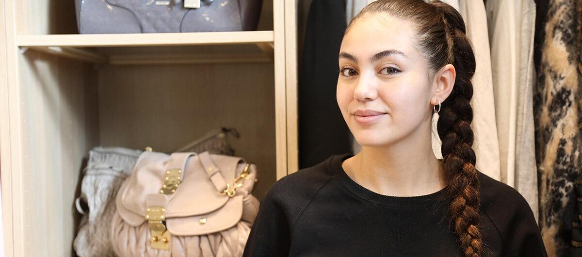 Nathalie som driver den nya vintagebutiken Walk in Closet i Täby Park står framför de fina kläderna i butiken